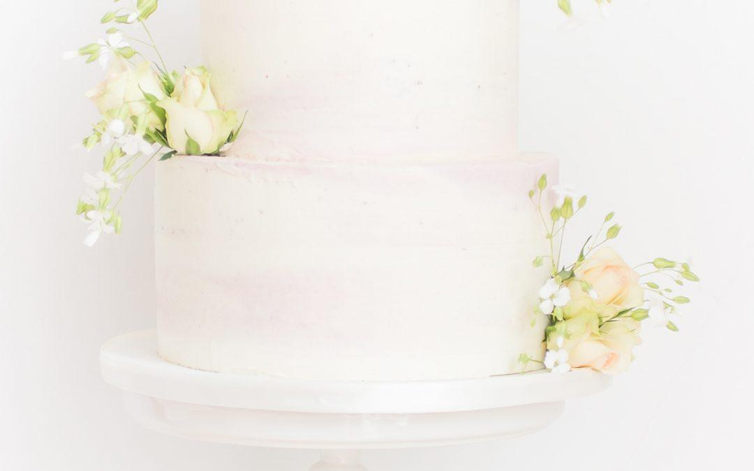 Zachtroze bruidstaart met echte bloemen